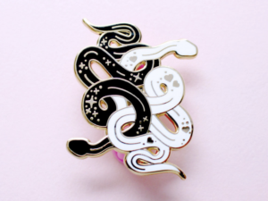snakes enamel pin on pink background